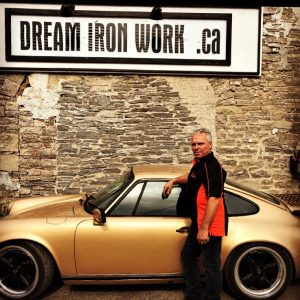 man standing infront of dream ironworks sign and car